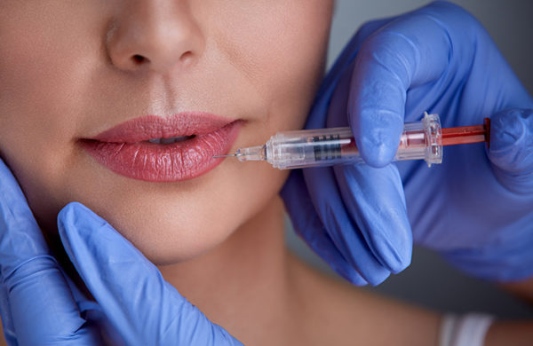 Close up of hands of expert injecting botox in female lips